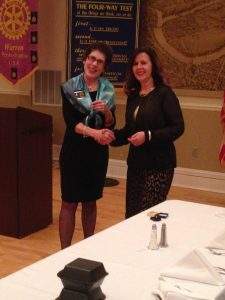 Rotary District 7280 Governor Patty Meehan awarding Afijete Bakalli with her Paul Harris Fellow + 3 pin.